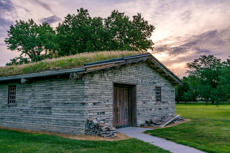 Military quarters made from mud bricks with a sod roof at sunrise. Dramatic skies of sunrise over a an old building with sod roof stock photos
