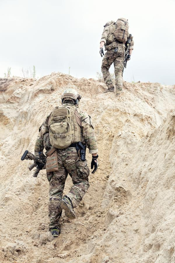 Military scouts walking through sands in desert royalty free stock photo
