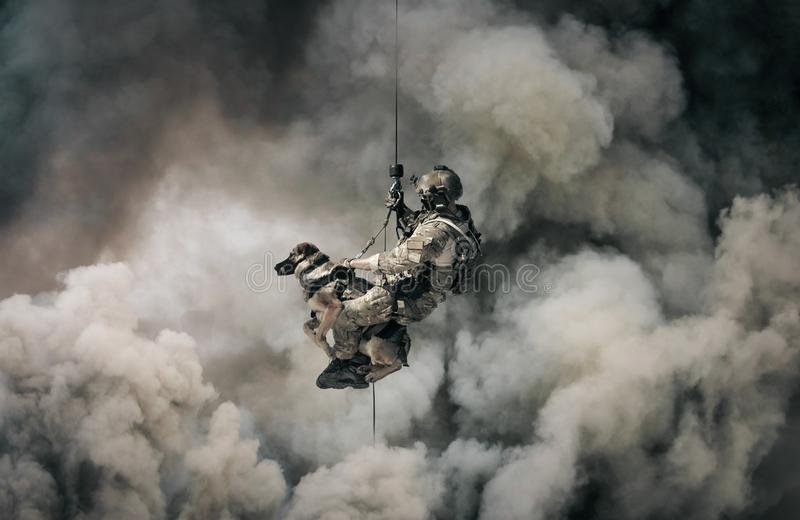 Military soldier with dog roping helicopter between smoke royalty free stock images