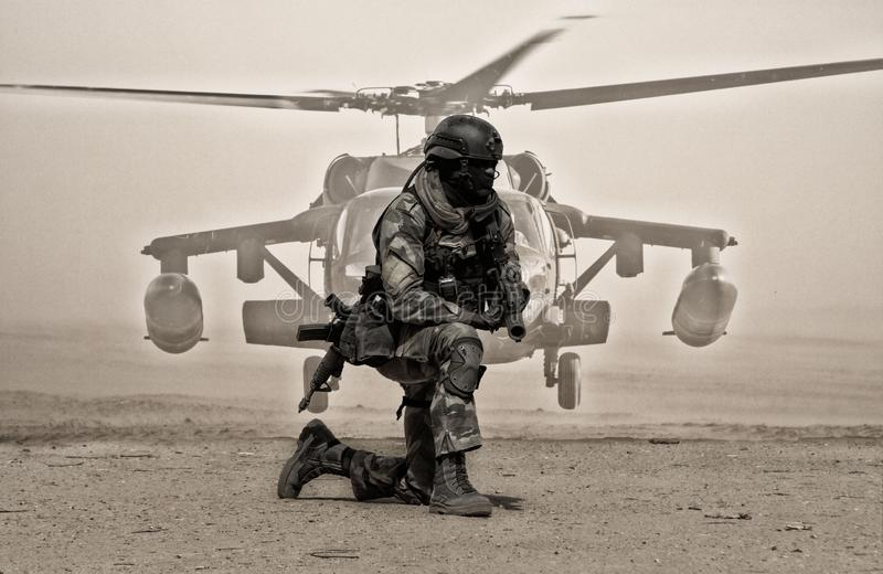 Military soldier between dust in front of helicopter stock image
