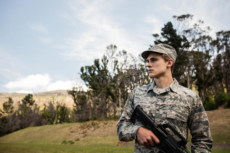 Military soldier guarding with a rifle. In a boot camp royalty free stock image