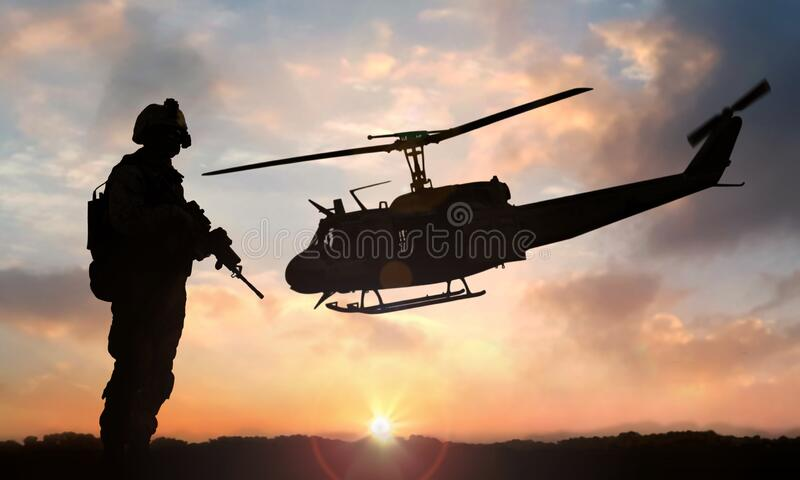 Military soldier standing on open field with automatic weapon in front of helicopter at sunset royalty free stock photos