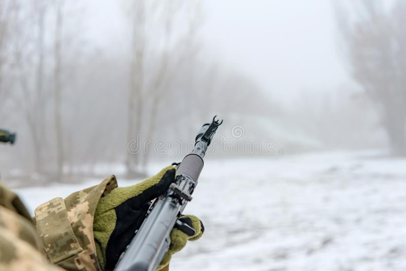 A military soldier takes aim with an automatic rifle and holds it in his mittens in winter royalty free stock photos