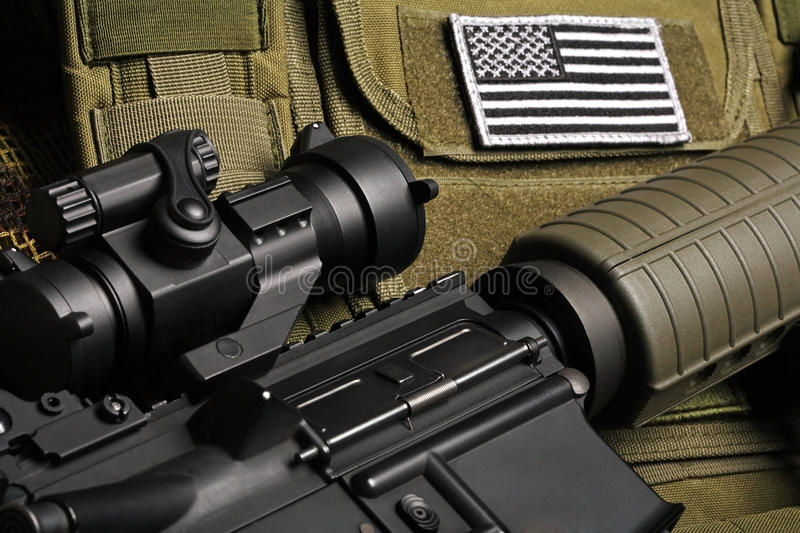 Military still life. Tactical vest with U.S. battle flag and assault rifle close-up royalty free stock photography