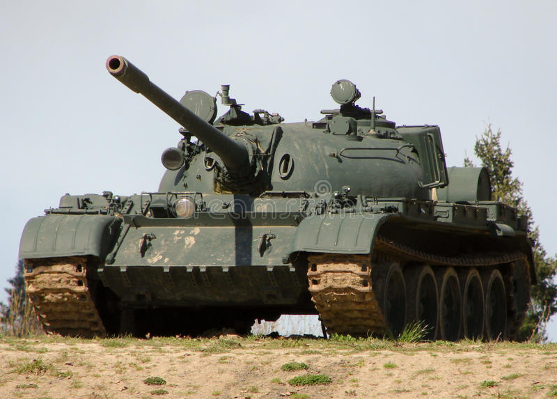 Military Tank. A green military tank coming over the crest of a hill royalty free stock image