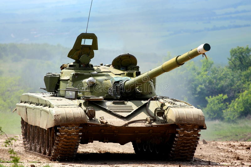 Military tank. A heavy military tank moving outdoor in a field