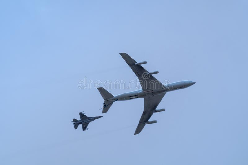 Military tanker aircraft refueler and fighter jets fly on blue sky royalty free stock photos