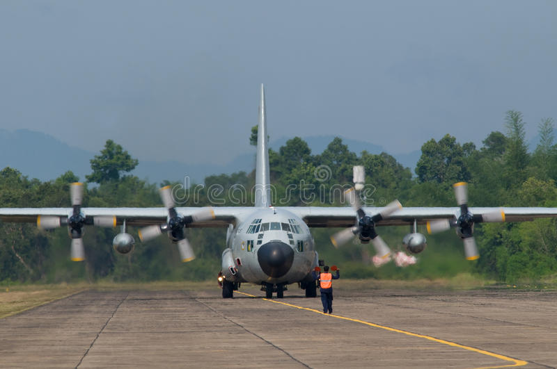 Military transport aircraft. At airport in tropical conditions, engines running. Distortions due to heat haze over the tarmac royalty free stock image