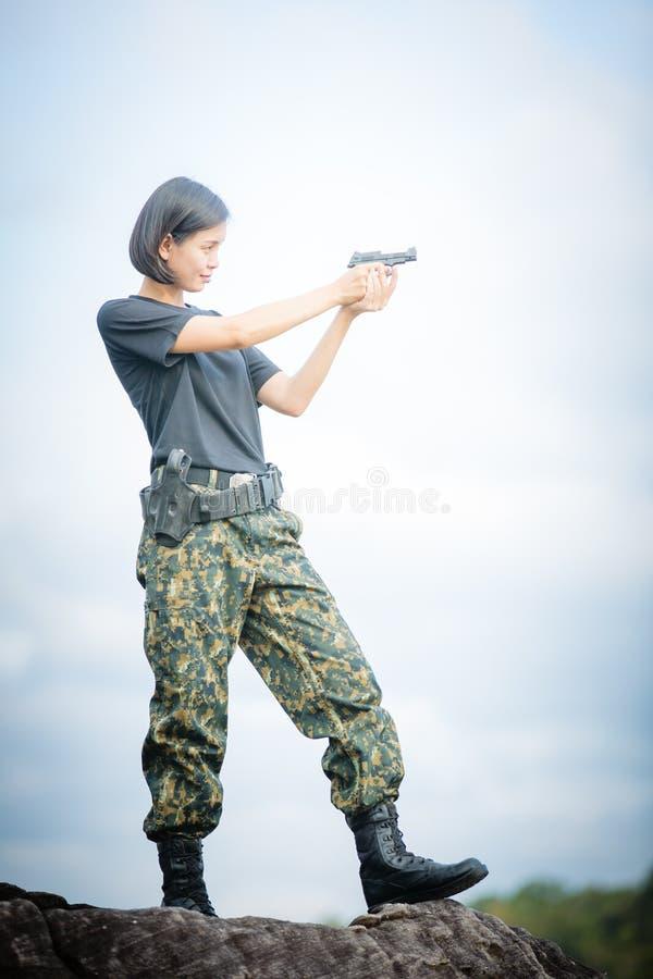 Military woman shooting a gun. Asian woman royalty free stock image