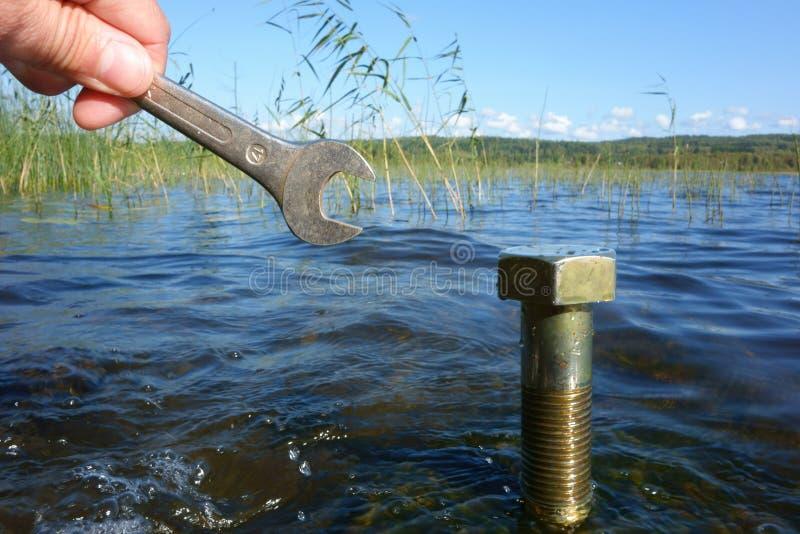 Miljö- begrepp: Hand med en skiftnyckel som är främst av en stor bult i en sjö arkivfoton