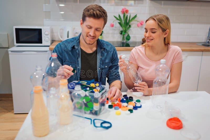 miljön skyddar Medvetna unga par som återanvänder tomma plast- flaskor och lock, medan sitta på tabellen med royaltyfri fotografi