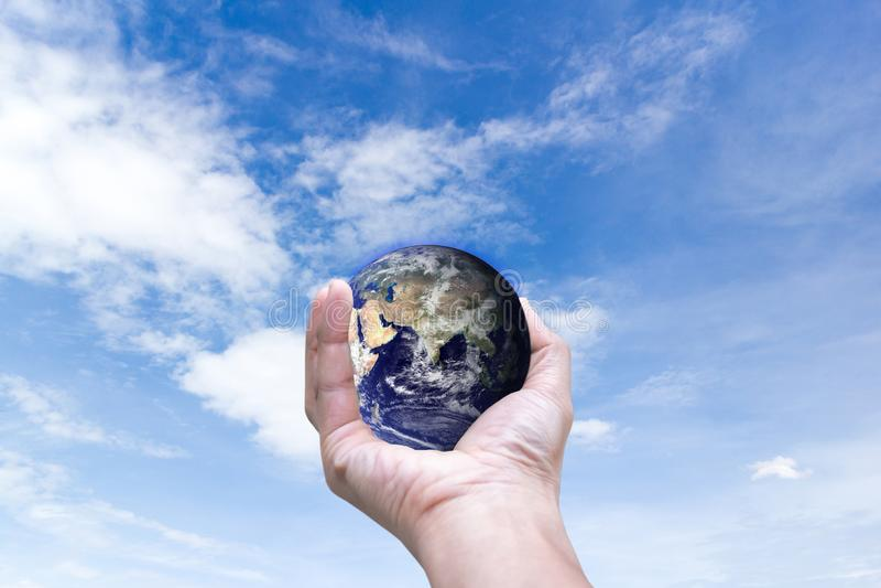 Miljövärld i händer som rymmer förälskelsejord och träd av beståndsdelar av detta bild som möbleras av NASA royaltyfri fotografi
