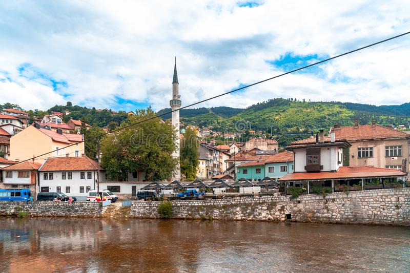Miljacka River and Bridges in Sarajevo. SARAJEVO, BOSNIA - AUGUST 3, 2019 : Houses near Miljacka river and bridges. The old town is most popular place for royalty free stock image