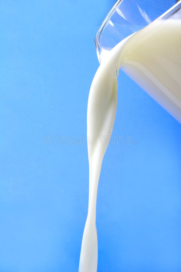 Milk. Pouring of milk from a jug royalty free stock images