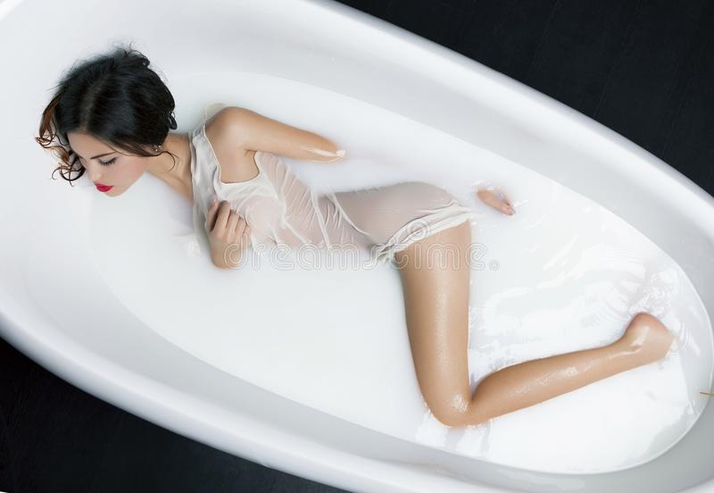 Milk Bath Spa and Woman in it. royalty free stock photography