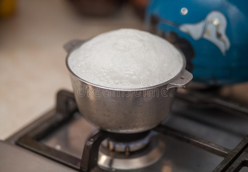 Milk is boiling over the saucepan royalty free stock photos