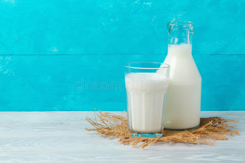 Milk bottle and glass on wooden table over blue background with copy space. Jewish holiday Shavuot royalty free stock photography