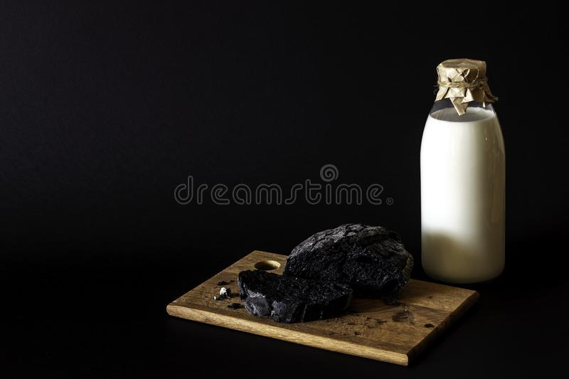 Milk and bread on a black background royalty free stock photography