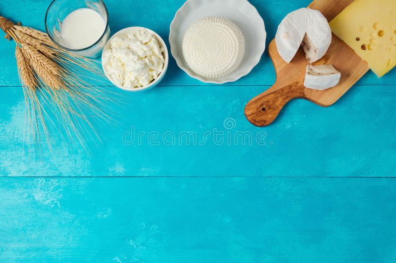 Milk and cheese, dairy products on wooden blue background. Jewish holiday Shavuot concept. View from above royalty free stock photos