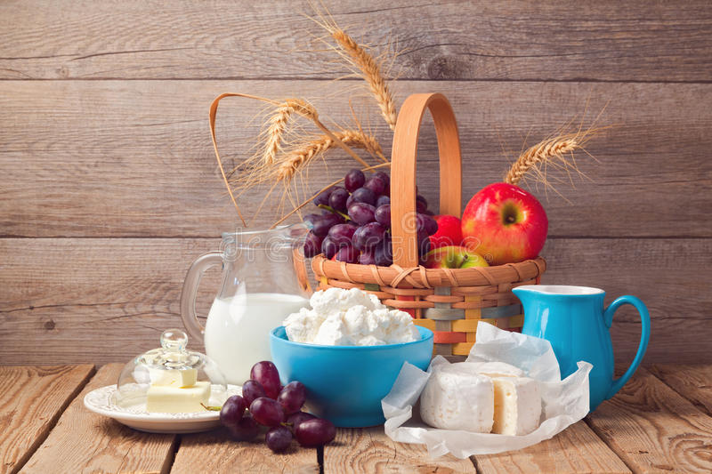 Milk, cheese and fruit basket over wooden background. Jewish holiday Shavuot celebration stock photos