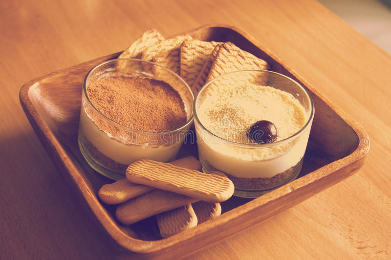 Milk cheesecake, decorated with cherries, in glasses with cookies in a wooden bowl on a wooden table on a blurred background in th stock image