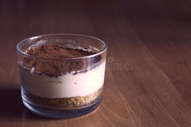 Milk cheesecake, decorated with coffee crumbs, on a wooden table on a blurred background in the early summer morning stock photo
