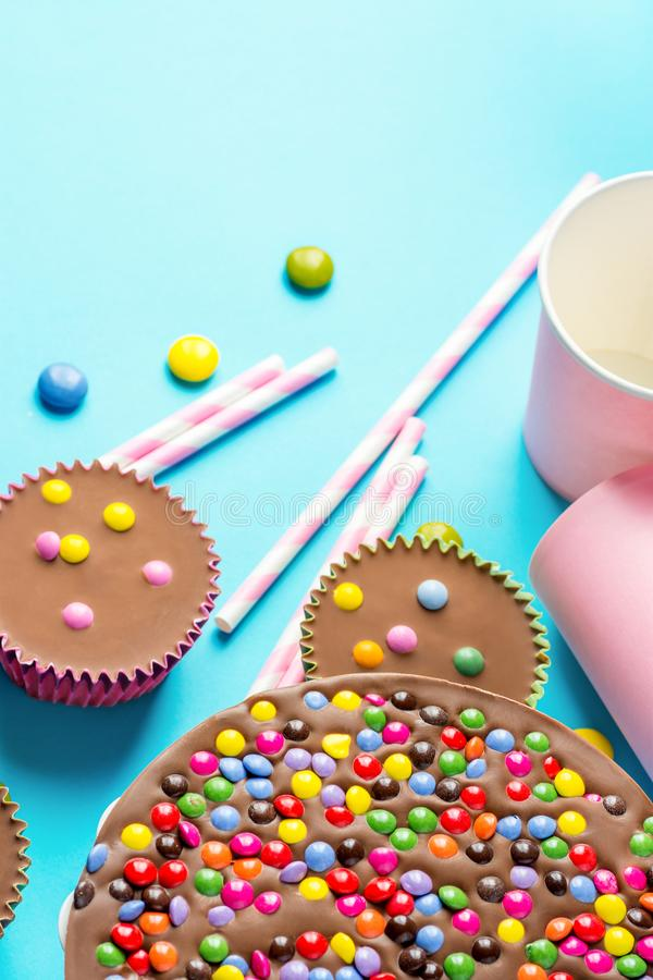 Milk Chocolate Birthday Cake with Multicolored Glazed Candy Sprinkles Buttercups Paper Drinking Cups Pink Straws Blue Background royalty free stock image