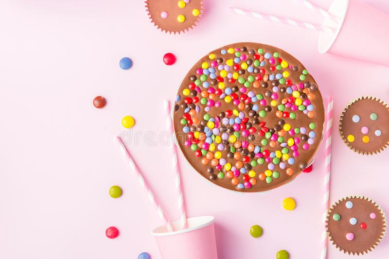 Milk Chocolate Birthday Cake with Multicolored Glazed Candy Sprinkles Buttercups Paper Drinking Cups Pink Straws Pink Background stock photography