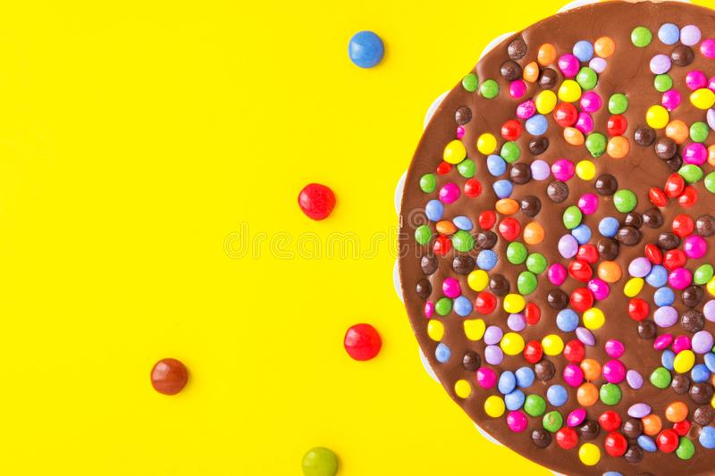 Milk chocolate birthday cake with multicolored glazed candy sprinkles decoration on bright yellow background. Kids party stock photos