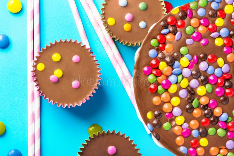 Milk chocolate birthday cake with multicolored glazed candy sprinkles decoration peanut butter cups on blue background. Kids party stock photo