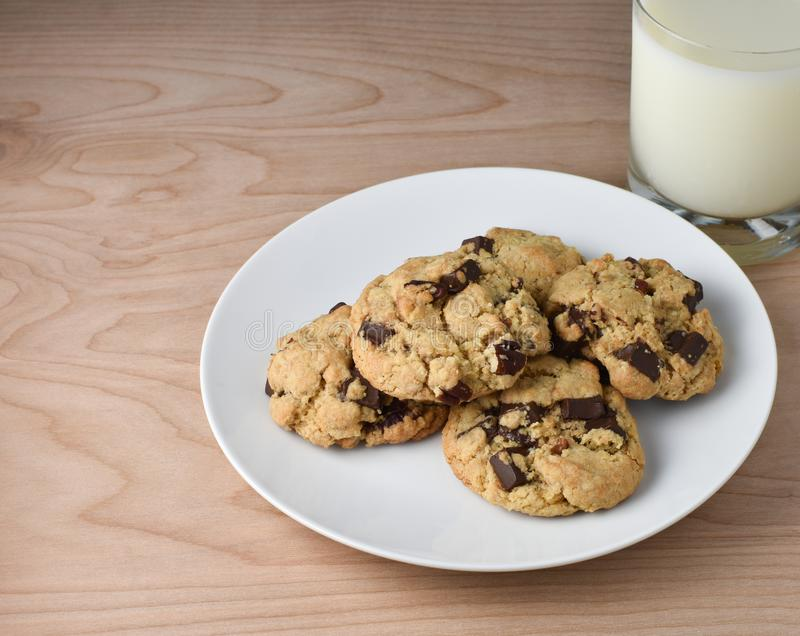 Milk and Chocolate Chip or Chunk Cookies on wood table. Close up of Chocolate Chunk Cookies with pecans and glass of white milk. Includes white plate on a stock photo