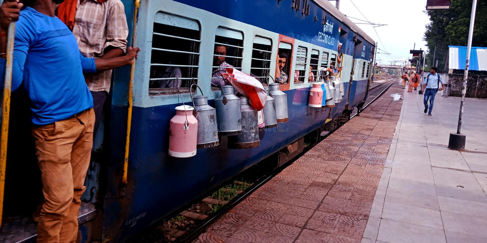 milk container hanging on milk boxes hanging out in train at indian railway station in india oct 2019 royalty free stock photos