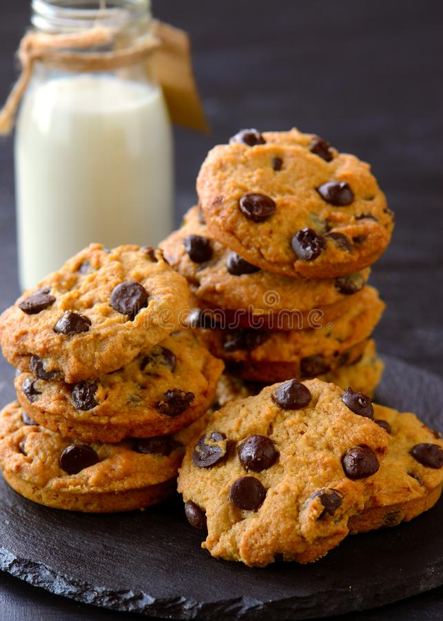 Milk and cookies. Bottle of milk and hot chocolate chip cookies stock photo