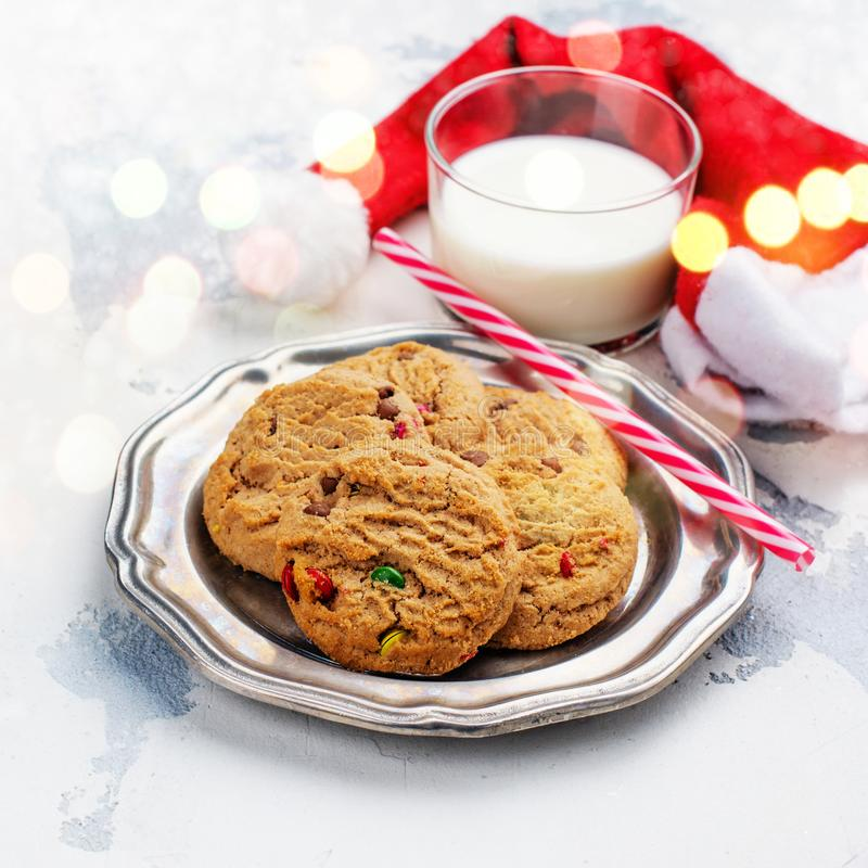 Milk and cookies for Santa Claus and Santa`s hat over wooden bac royalty free stock images