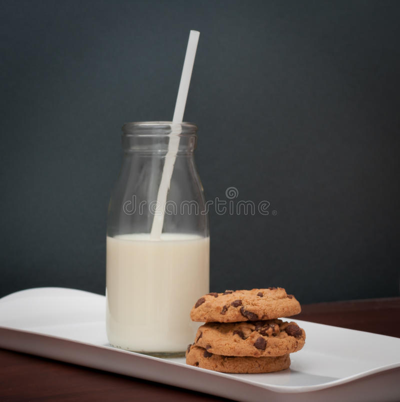 Milk and cookies on serving tray. Small glass retro milk bottle with straw and chocolate chip cookies on a white serving tray stock photos