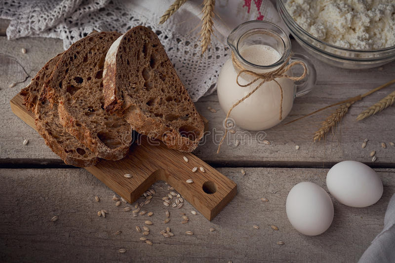 Milk, cottage cheese, sour cream, multigrain homemade bread, fresh eggs and wheat on rustic wooden background. stock photography