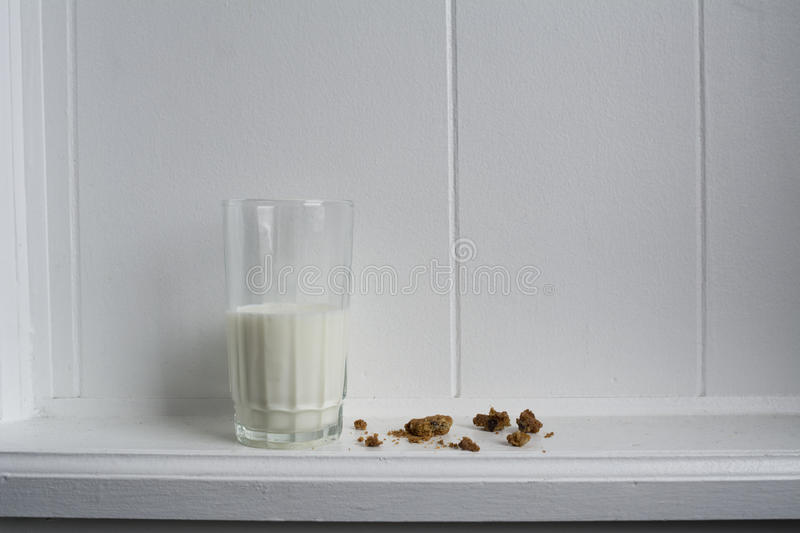 Milk and Crumbled Cookies. Glass of milk sitting on white wood ledge with crumbles chocolate chip cookie royalty free stock photos