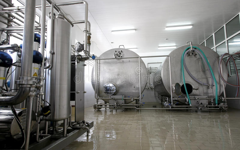 Milk and dairy factory interior. Stainless steel controlled pressure tanks in dairy factory