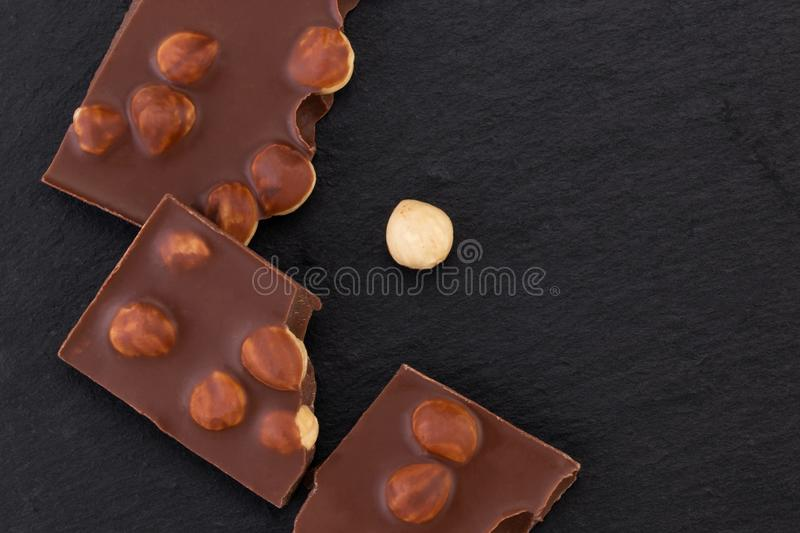 Milk or dark chocolate with nuts on black background.  stock photo