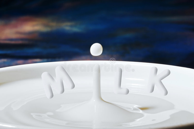 Milk drop or droplet dripping into a bowl full with letters added to make'Milk' royalty free stock photos