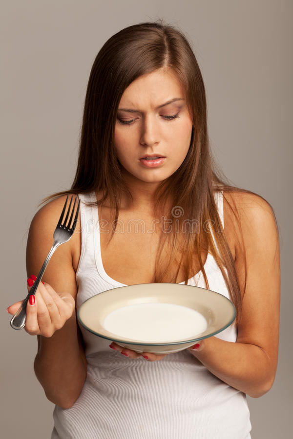 Milk and fork. Girl is asking if it is possible to eat milk with fork royalty free stock photos