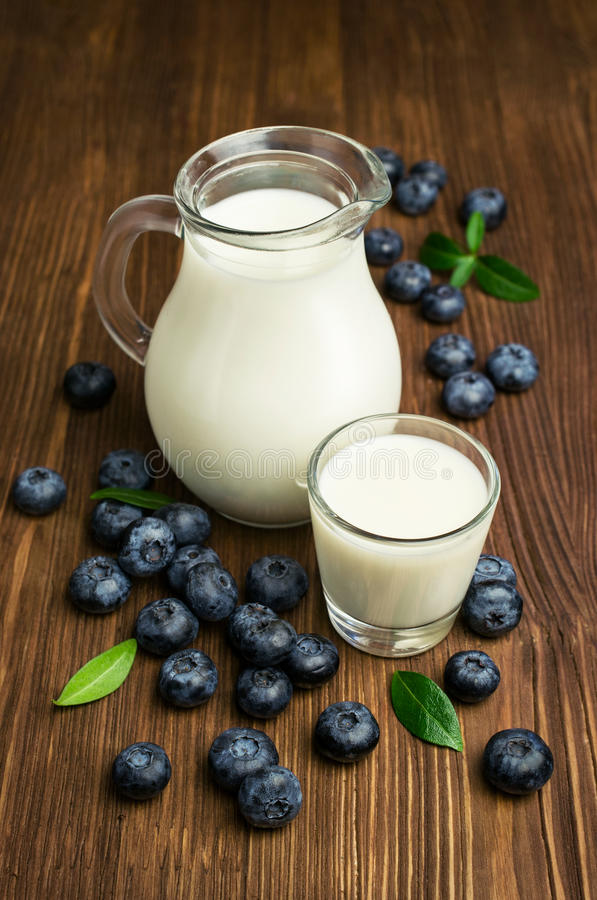 Milk and fresh blueberries stock images