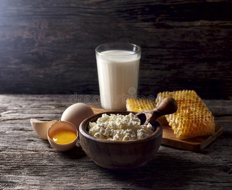 Milk in glass, honeycomb and eggs on a wooden background. Cottage cheese in a wooden bowl, rustic style. Dairy products in the mo stock photography