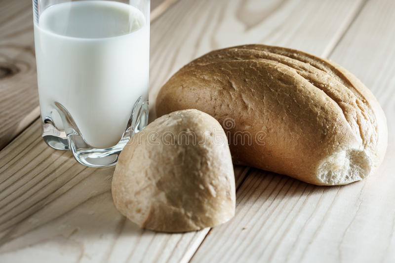 Milk in a glass jug. Bread on wooden background. Bio products. Food. royalty free stock image