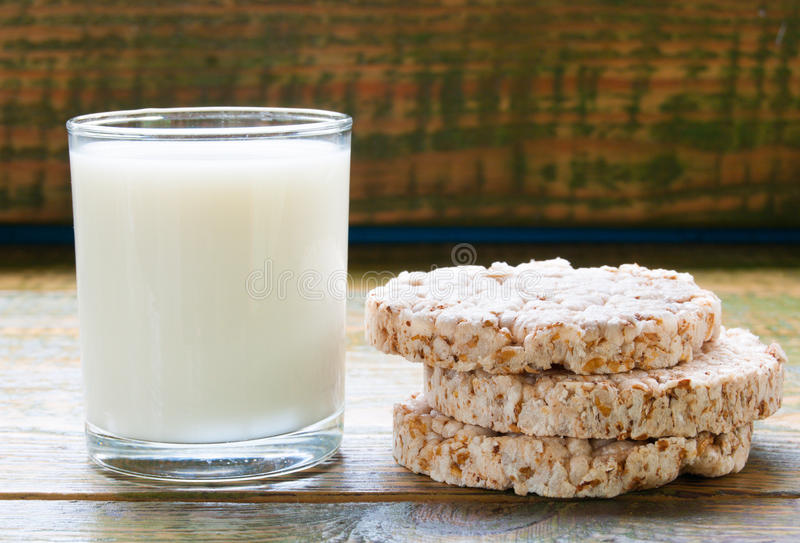 Milk in glass mug with Crispbread on wooden table. Concept of easy morning breakfast royalty free stock photography