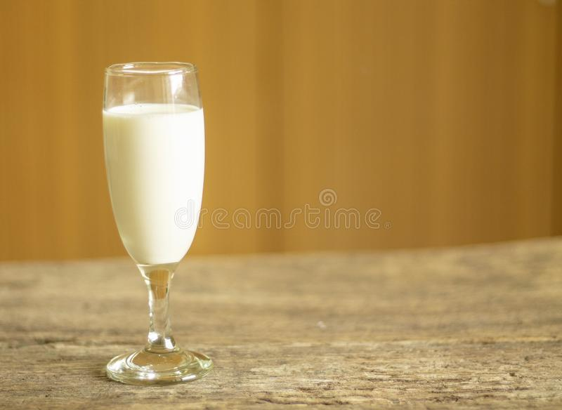 Milk glass placed on a wooden background stock images