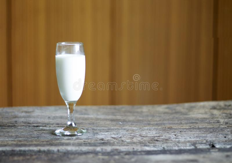 Milk glass placed on a wooden background stock photos
