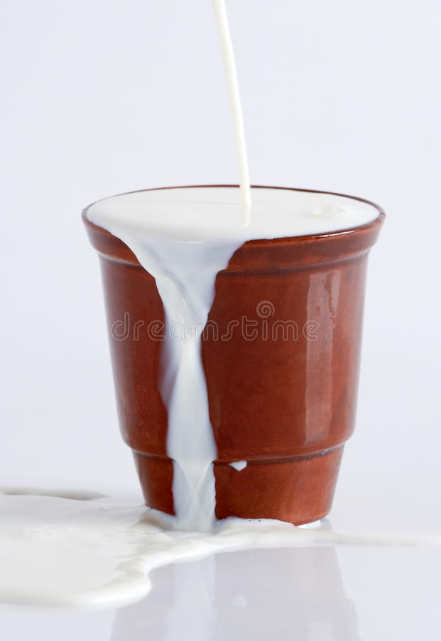 Milk hällde från en lerakopp royaltyfri bild