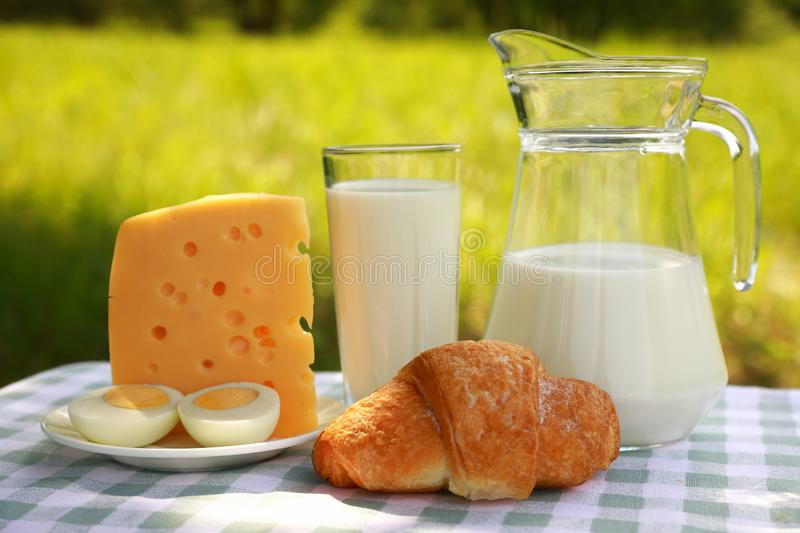 A milk jug, a glass of milk, a piece of cheese and a cut egg on a plate, and a croissant on a green-and-white checkered tablecloth. Breakfast composition of a stock photo