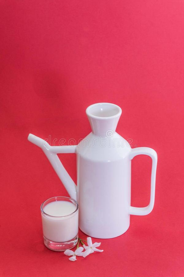 Milk Jug. Still life composition with a white porcelain jug of milk, a small glass, and some jasmine flowers again a red background stock photos